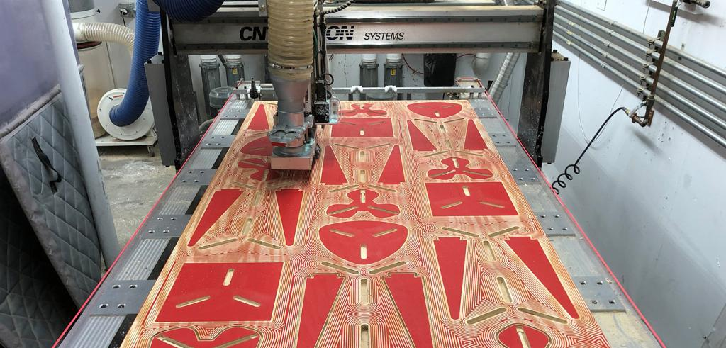 A wooden panel with red designs on it is milled by a robotic arm.