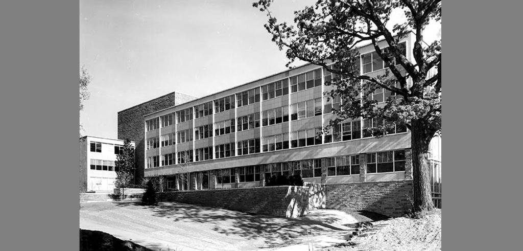 Balck and white photo of a four-story academic building with a facade of many windows