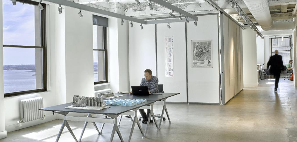 a man sitting at a computer in a long white room