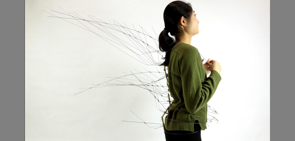 A woman with wires attached to and projecting from her clothing