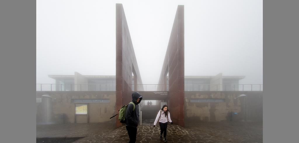 Two students outside a building in the fog