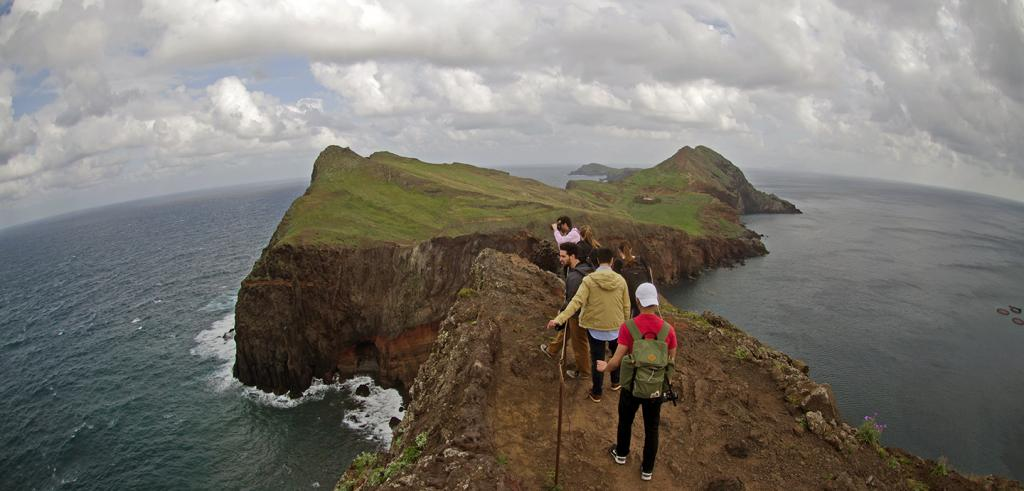 Students hiking on a rocky peninsula above the sea