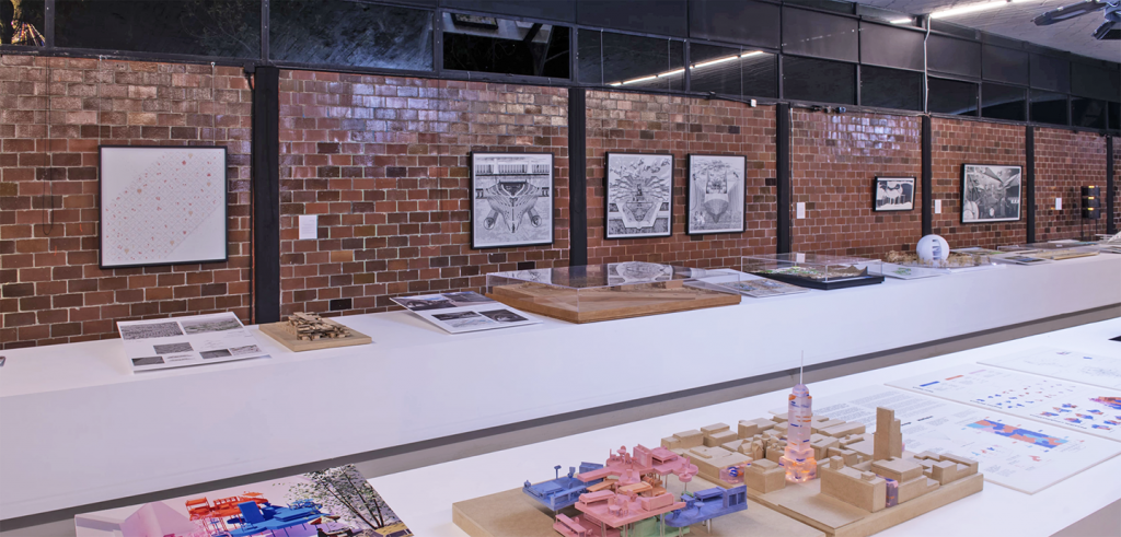 Long tables and a red brick wall displaying 20 architectural drawings and models