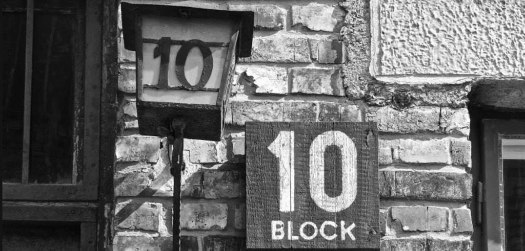 Black and white photo of a side of a building with the number ten written on a block and lamp post.