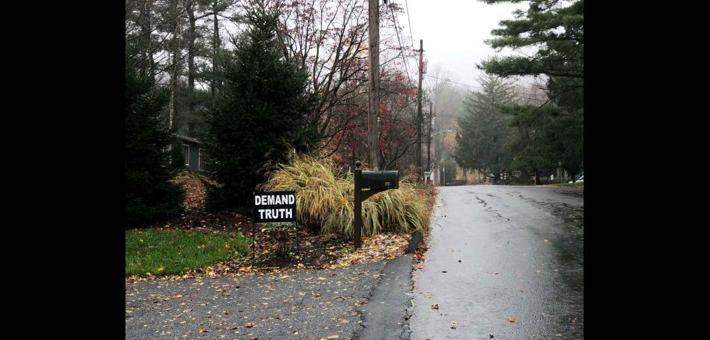 A wet road on one side with the corner of someone's property and a black Demand Truth sign out front next to a mailbox.
