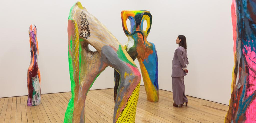 Four abstract sculptures in different bright colors on wooden floors with a woman looking at a sculpture.