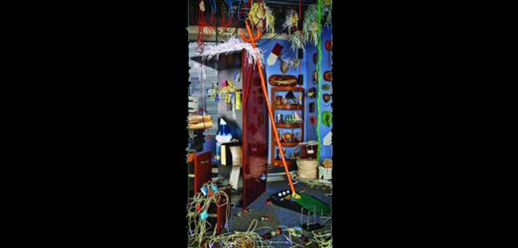 Miscellaneous objects in a room with bright blue walls cluttered together, various wires hanging from ceiling, humidifier, nick knacks on the walls.