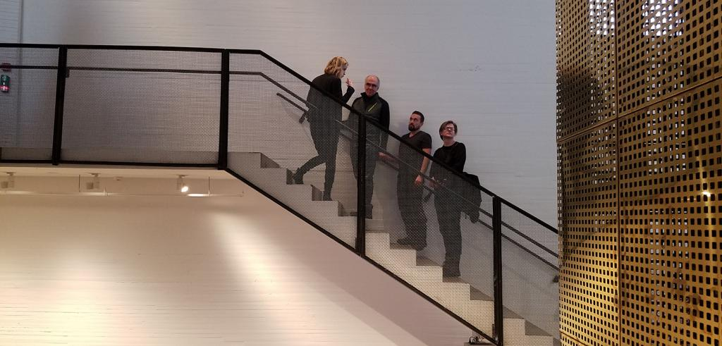 Four people standing in a line on a staircase against a white wall with black steel railings