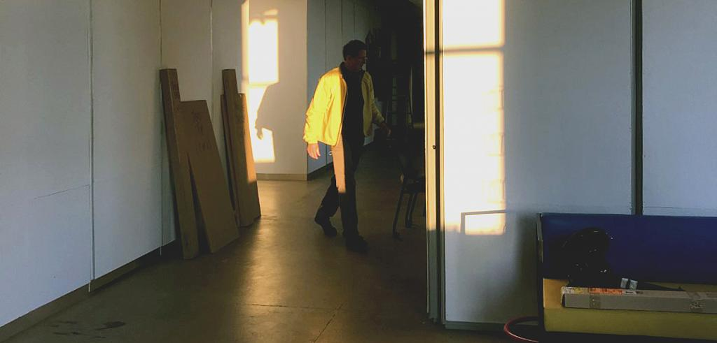 A man in a yellow jacket walking through a shaft of sunlight in an interior space with boxes propped against the walls.