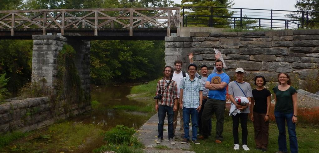 Group of people standing to the right of a stone aquaduct