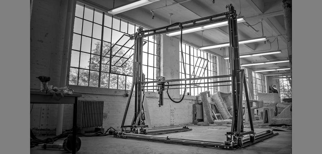 Industrial machine on a rectangular gantry inside building with large glass windows