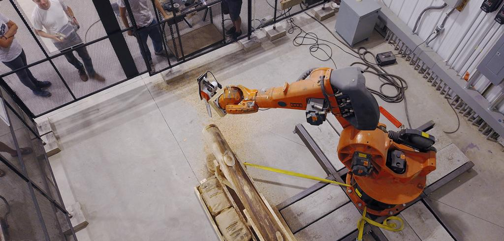 men watch a a robotic arm shaping wood