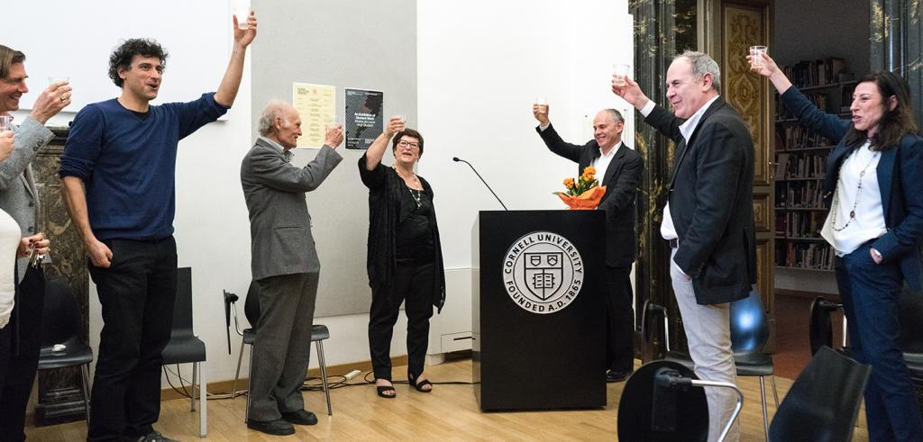 Several people standing in a room raising a celebratory glass to cheers
