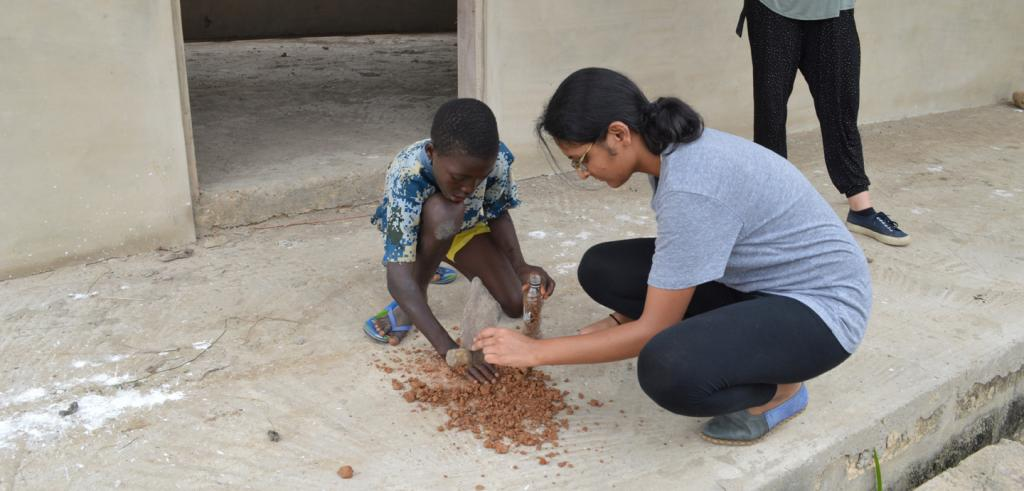 A child and a woman play with gravel at a construction site