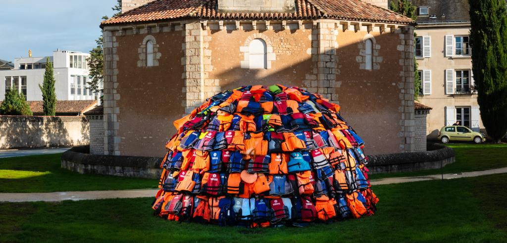an igloo constructed of colorful lifejackets with an octagonal stone building behind it