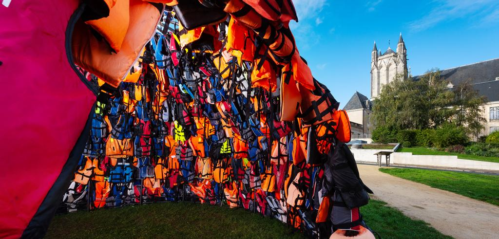 interior view of an igloo constructed of colorful lifejackets with a medieval church tower in the background