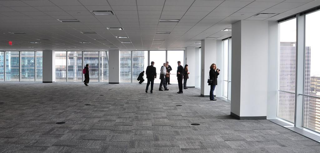 A group of people in an unfurnished high rise space, with glass walls that look out on the city