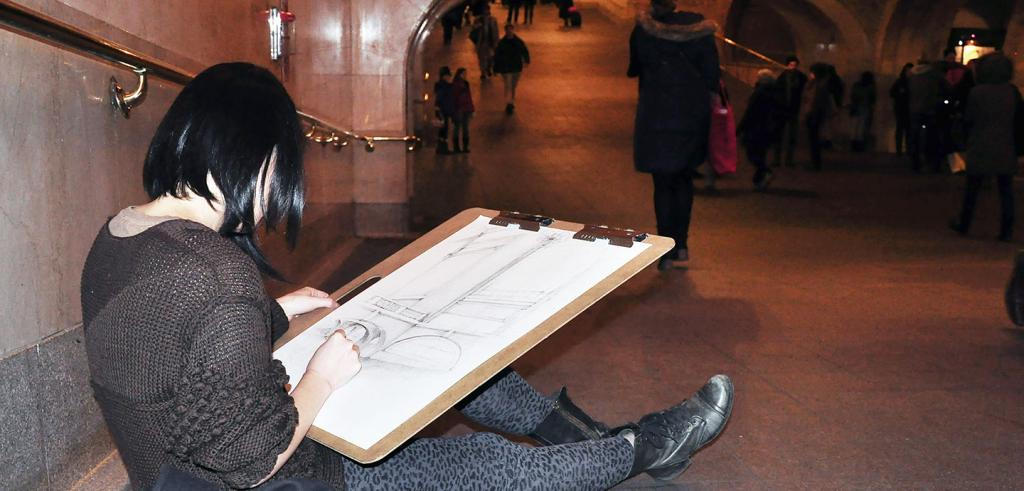 student sitting on the floor and sketching in train station