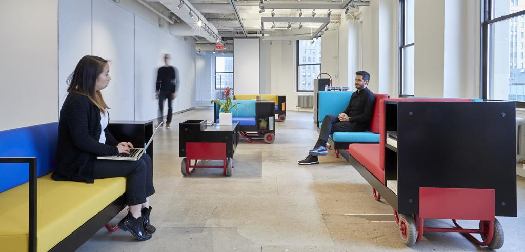 Two people sitting on separate couches and one person walking towards them
