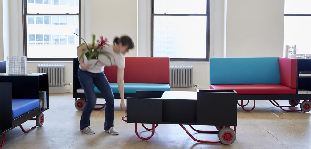 a woman moving furniture in an office while holding a plant