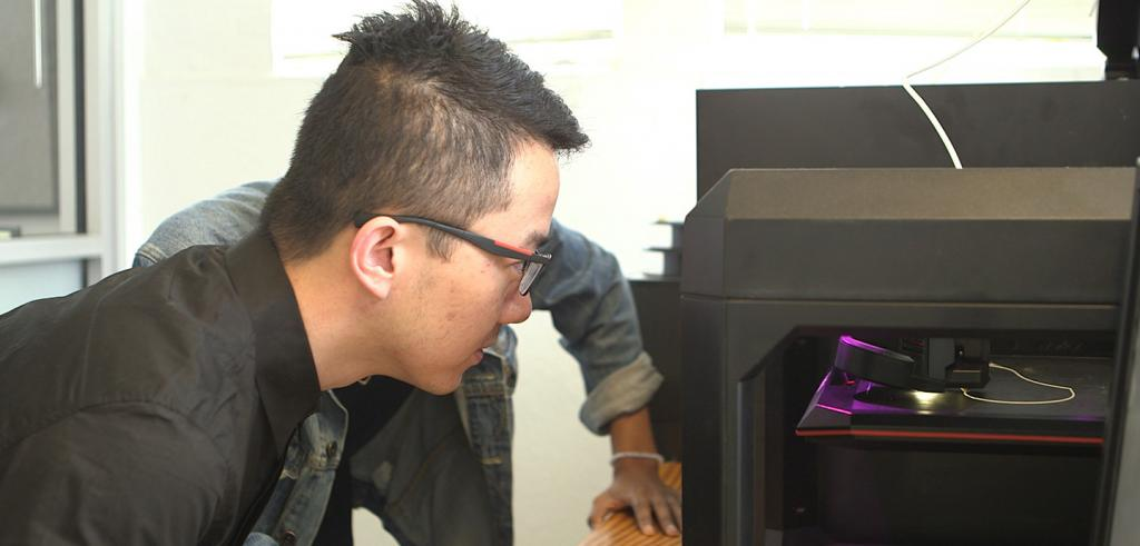 a student looking into a 3D printer