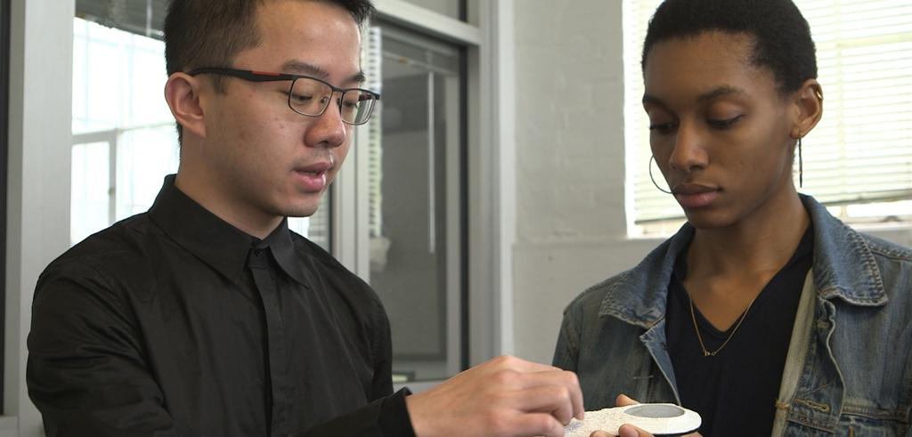 two students discussing the insole of a shoe