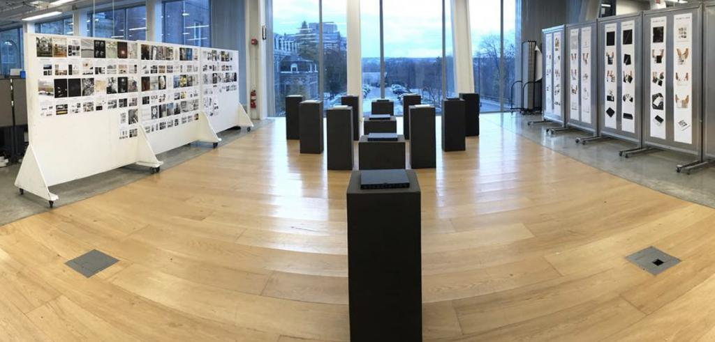a gallery space with floor-to-ceiling windows and artwork on pedestals and pinned to screens
