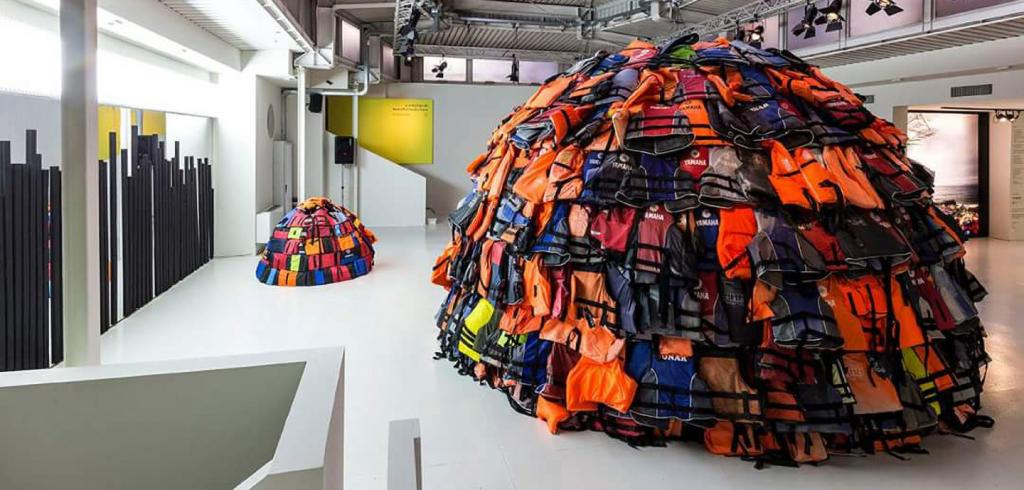 two igloos constructed from colorful lifejackets in a modern industrial-style exhibition space