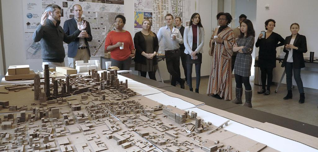 A group of people gathered around a cardboard cityscape.
