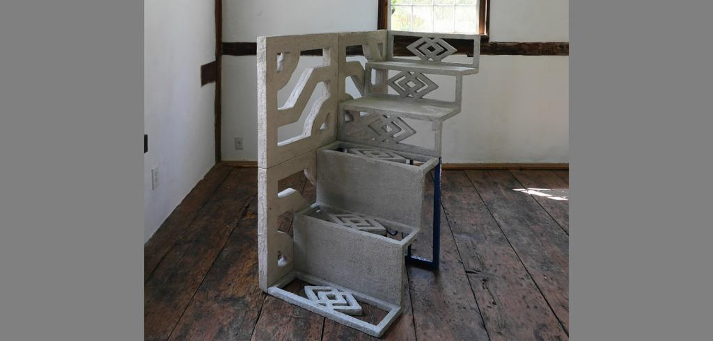 a freestanding flight of five stairs with decorated treads, risers, and handrail in the middle of a room