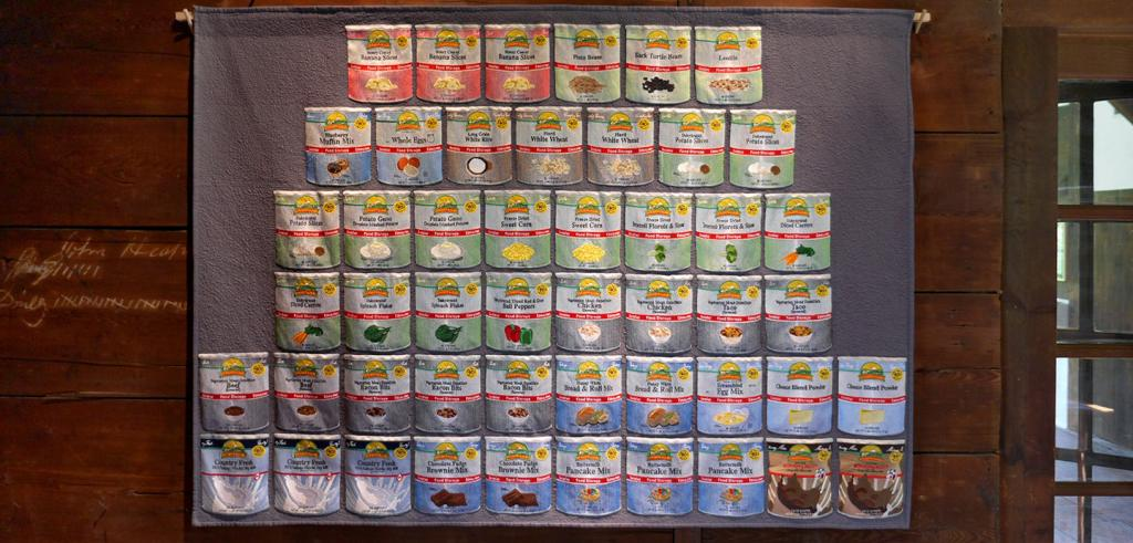 An embroidered panel depicting six stacked rows of canned food