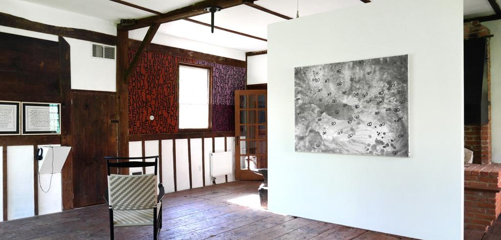 A large painting of winged bugs on a white wall in a room with wood paneled walls and a rattan chair.