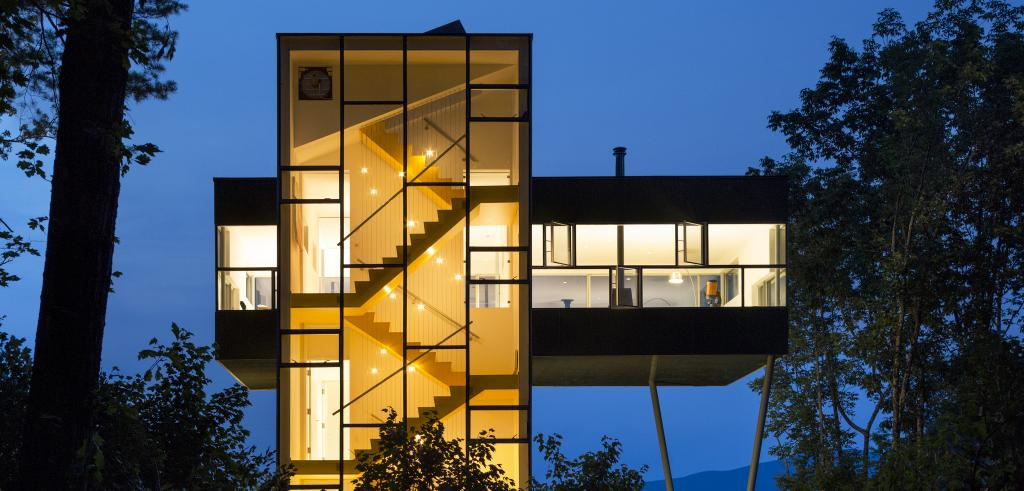 glass tower house with visible staircases lit from inside at night