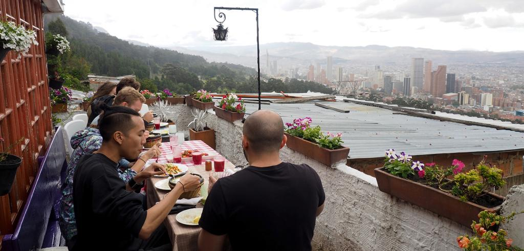 Architecture graduate students share a meal with a local family living in an informal neighborhoods in Bogotá's Los Cerros Orientales
