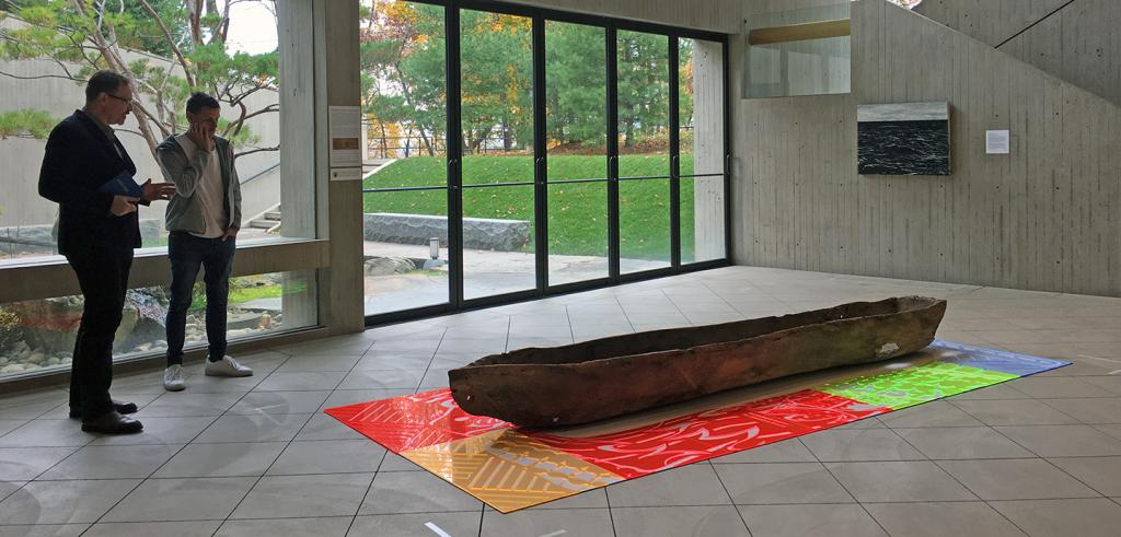Two men observe an artwork depicting a 3-dimensional canoe on a colored mat, in a museum gallery