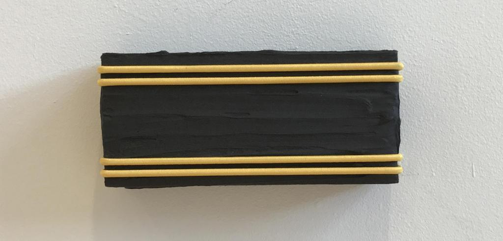 A black painting with two thin yellow lines on the top and bottom of it.