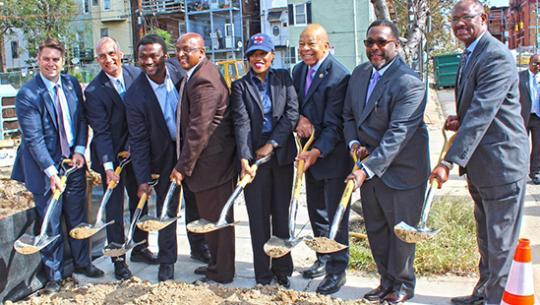 men and one woman in suits breaking ground on a site by ceremoniously shoveling dirt