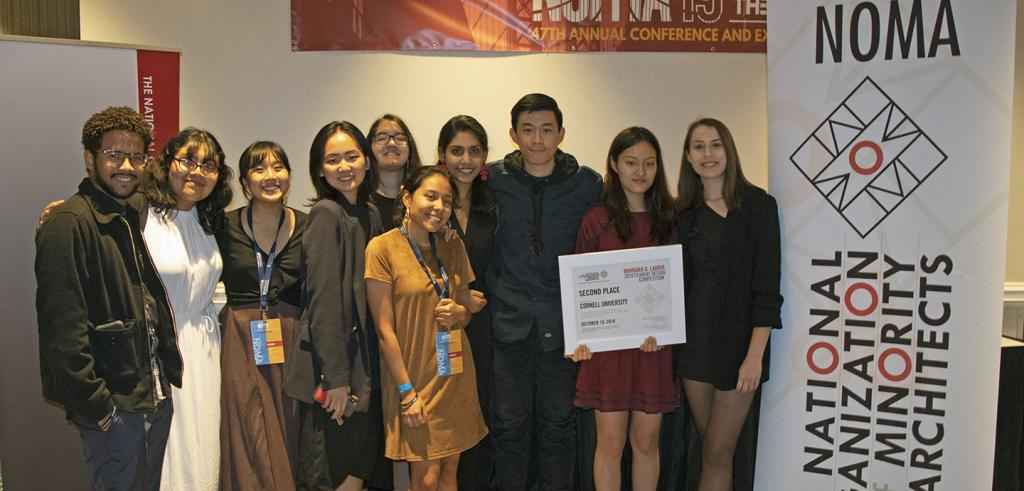 Ten young people pose with a certificate next to a conference banner