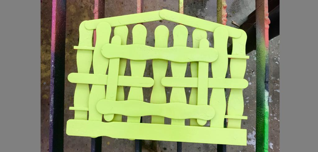 Lime green wavy Popsicle sticks layered together to form a house set against a spray painted street background.