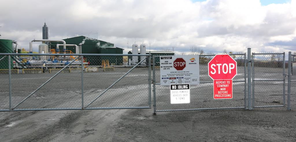 a fenced industrial site with stop signs attached to the chain link fence