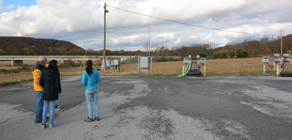 Three people stand on an asphalt pad near gas pipeline relays