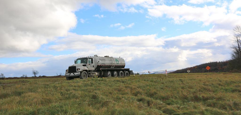 A tanker truck on a grassy hill