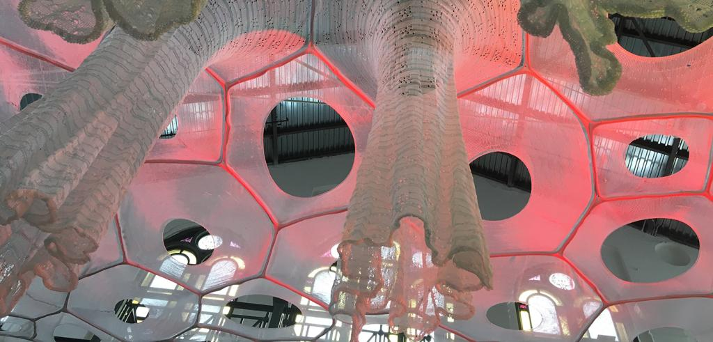 detail of knitted fabric in a web like configuration with longer tubes dropping from the center