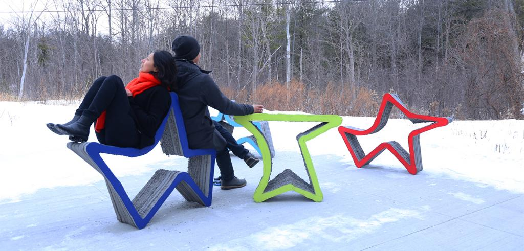 Two people seated on a blue star-shaped chair in the snow, with three more brightly colored chairs in background