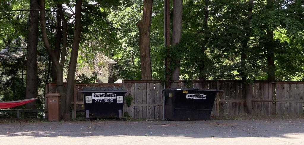 Two casella dumpsters against a wooden fence in near a wooded area.