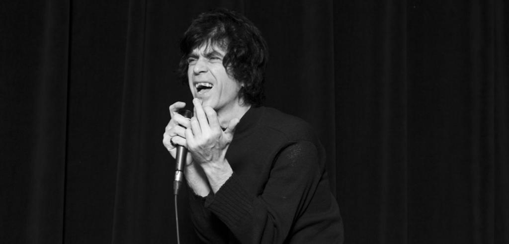 Black and white image of a man singing into a microphone