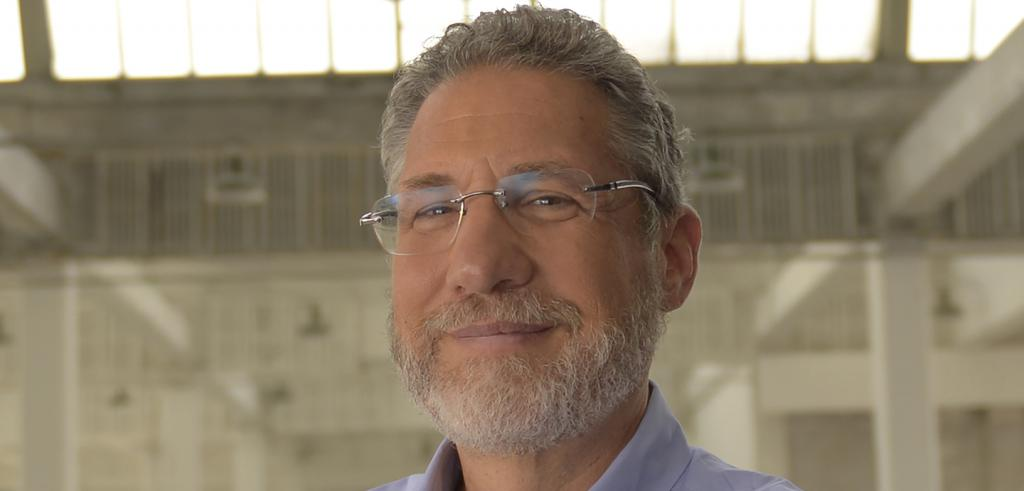 A man's face with a beard and wearing glasses