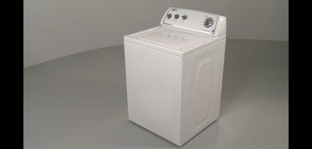 white washing machine sitting in grey space