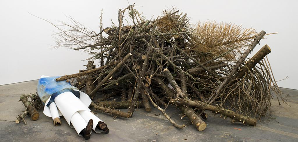 A pile of dried sticks and branches with a replica of a body lying alongside