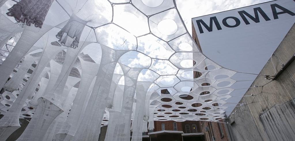 tubular fabric structures suspended in a courtyard with MoMA written on a wall behind it